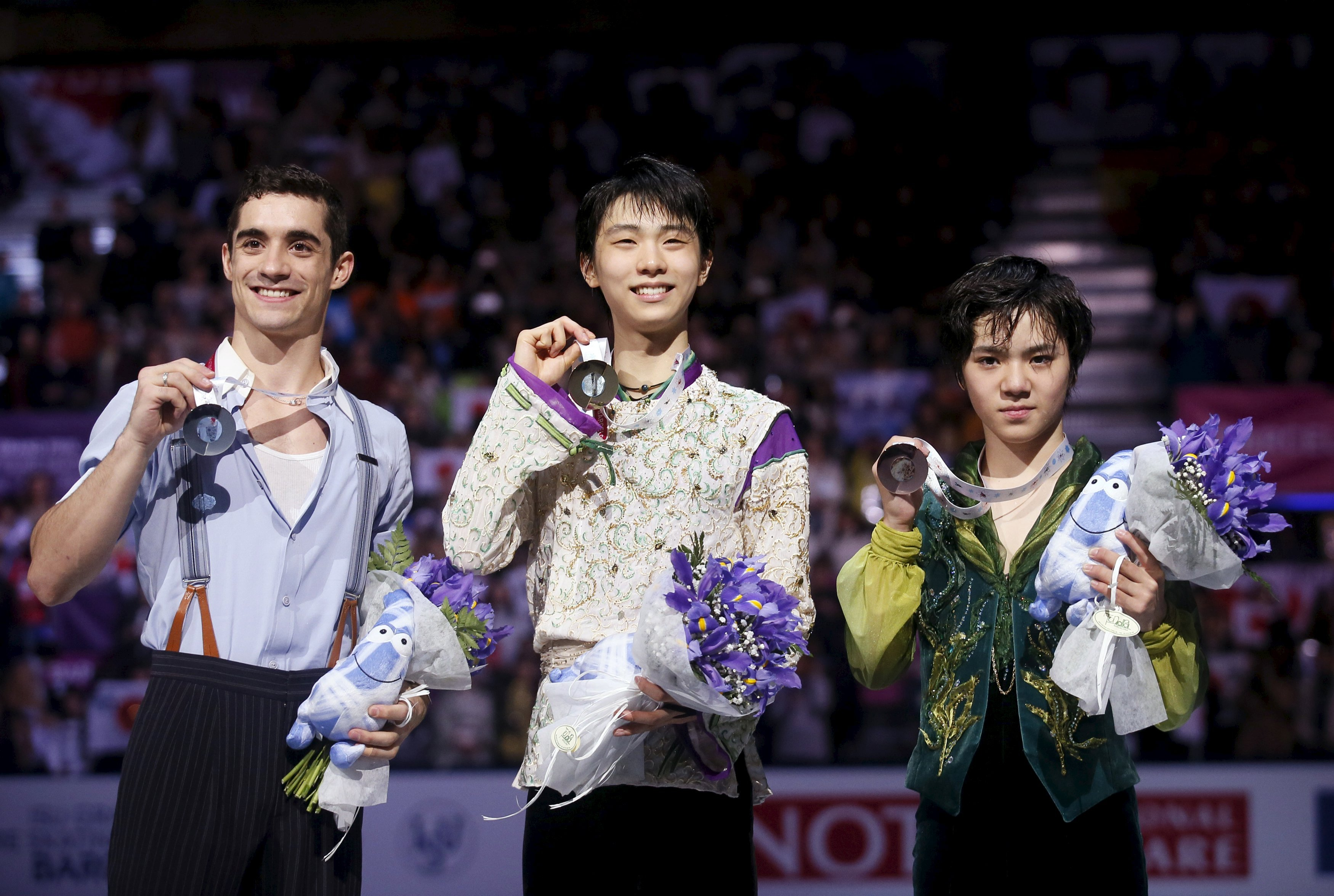 Gold medal winner of the men's free program Yuzuru Hanyu (C) of Japan, silver medal winner Javier Fernandez (L) of Spain and bronze medal winner Shoma Uno of Japan during the medal ceremony at the ISU Grand Prix of Figure Skating final in Barcelona, Spain, December 12, 2015. REUTERS/Albert Gea